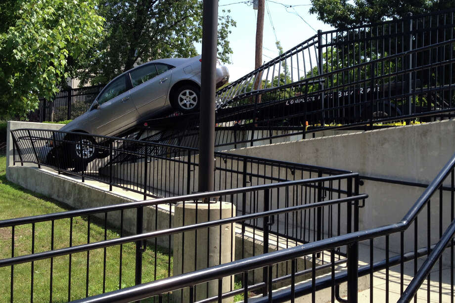 A gray Nissan lost control on Mill Hill Avenue, knocking down part of the iron fence at the side of the Bridgeport Hospital emergency room, July 7, 2014. The occupants of the car, a man and a woman, who were not on their way to the hospital when the accident occurred, were taken to the emergency room, evaluated and released. Photo: Frank Juliano / Connecticut Post