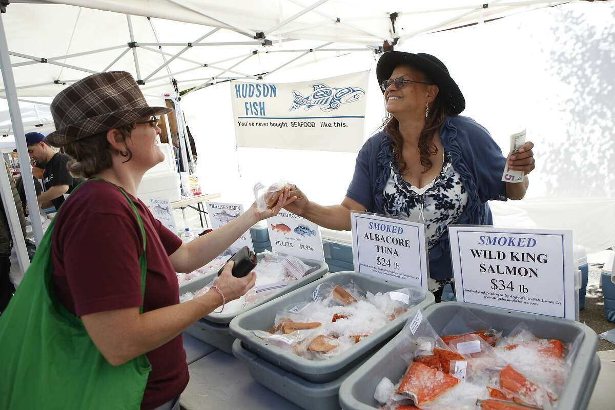 Yvette Hudson, right, of the Hudson Fish Company hands Tanya Stiller the smoked Albacore she just purchased at the North Berkeley Farmer's Market in Berkeley, CA, Thursday June 26, 2014.