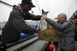 Fisherman Jay Karpinski loads a king salmon into the bag of customer Leo Wu of San Jose at Pillar Point Harbor in Half Moon Bay, CA, Saturday, June 28, 2014.