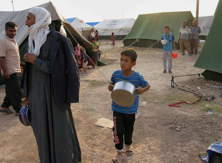 Iraqis displaced from towns attacked by Islamic militants wait for food distribution Sunday at a camp in Khanaqin, 90 miles northeast of Baghdad. After its initial blitz, the insurgent onslaught has eased. Photo: Adam Hadei, Associated Press