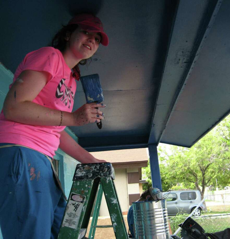 Emily White of the Schertz United Methodist Youth Fellowship pauses painting the porch of a home in McAllen. Photo: Courtesy / Schertz UMC