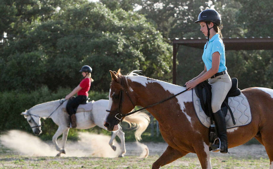 Katie Heiman, 12, right, and Betsy Karako, 18, take riding lessons at Esperanza Farms, 12037 FM 1560 N in Helotes, last week. Photo: Photos By Marvin Pfeiffer / Helotes Weekly / Express-News 2014