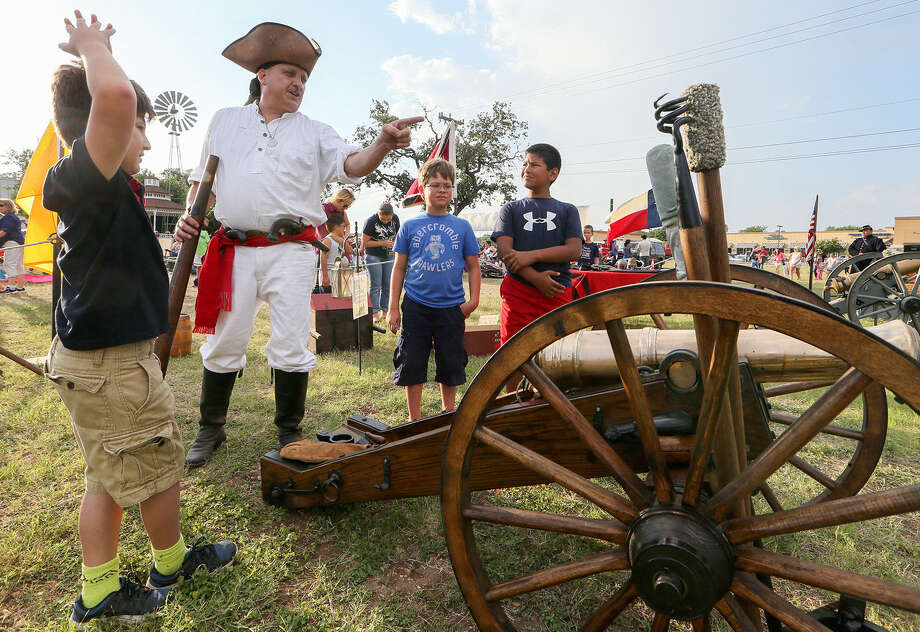 Jonathan Connelly, second from left, shows a replica three-pound French cannon used in the War of Independence to, from left, Ethan Pena, 9; Brayden Barnhard, 10; and Jayden Castillo during Helotes' Independence Day Celebration Saturday. Photo: Marvin Pfeiffer / Helotes Weekly / Express-News 2014