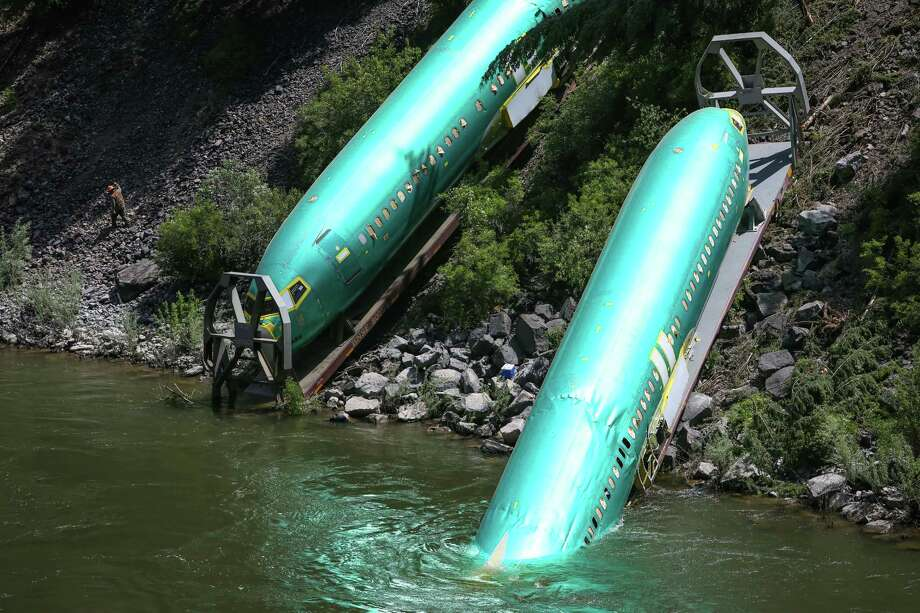 Work crews remove one of three Boeing 737 fuselages that plunged into the Clark Fork River east of Superior, Montana along Interstate 90. By Monday one had already been removed and crews had heavy equipment up a steep embankment hoisting another. The planes ended up down the steep embankment after the train hauling them to the Seattle area for final assembly derailed. Photographed on Monday, July 7, 2014. Photo: JOSHUA TRUJILLO, SEATTLEPI.COM / SEATTLEPI.COM
