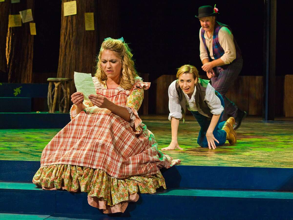 Celia (Greta Wohlrabe, left) reads one of the silly love letters to Rosalind, as Rosalind (Julia Coffey) sneaks up on her and Touchstone (Mike Ryan) looks on in Santa Cruz Shakespeare's