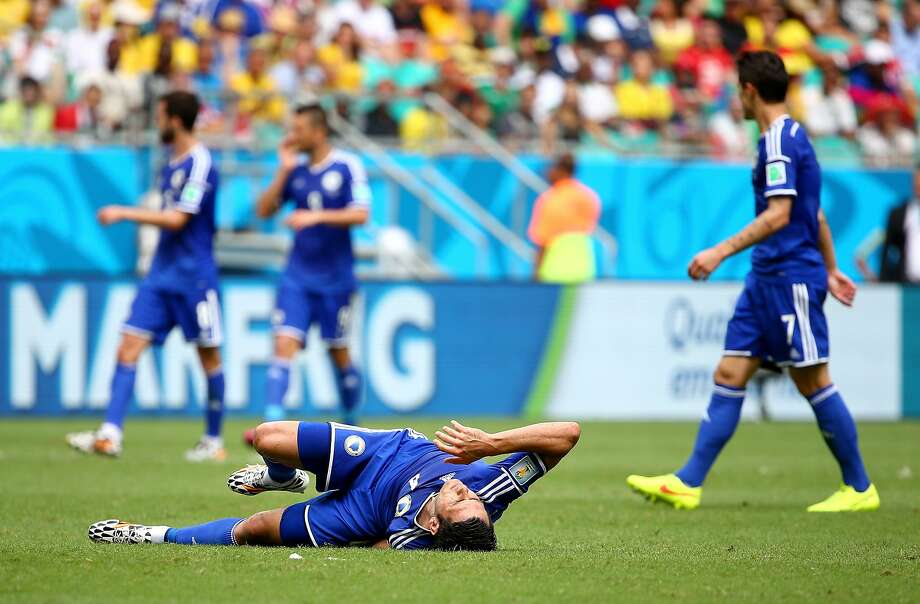Teammates of Emir Spahic of Bosnia and Herzegovina don't look too worried about him here ... Should they be?Verdict: Spahic was taken off the field on a stretcher after incurring a badly swollen foot.  Photo: Robert Cianflone, Getty Images