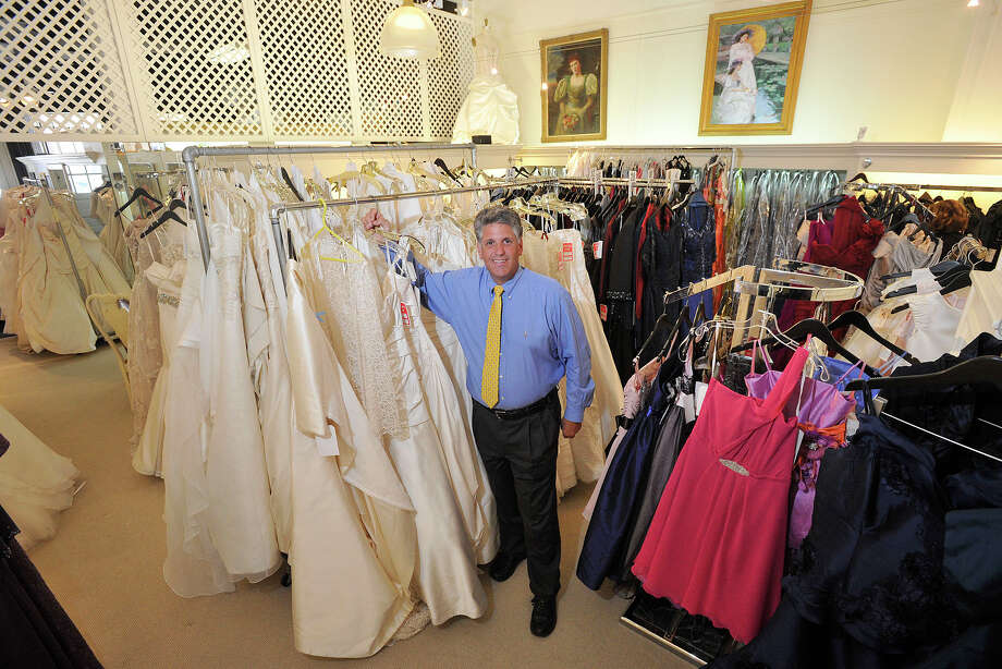 Owner Cory Fontana poses next to dresses at his store, Fontana Couture, in Greenwich, Conn., on Monday, July 7, 2014. Fontana Couture will be having a massive sale; selling their wedding dresses, that normally sell for over $4,000 or more, for $99; and party dresses starting at $50 during the Greenwich Sidewalk Sale Days starting this Thursday running through Sunday. Photo: Jason Rearick / Stamford Advocate