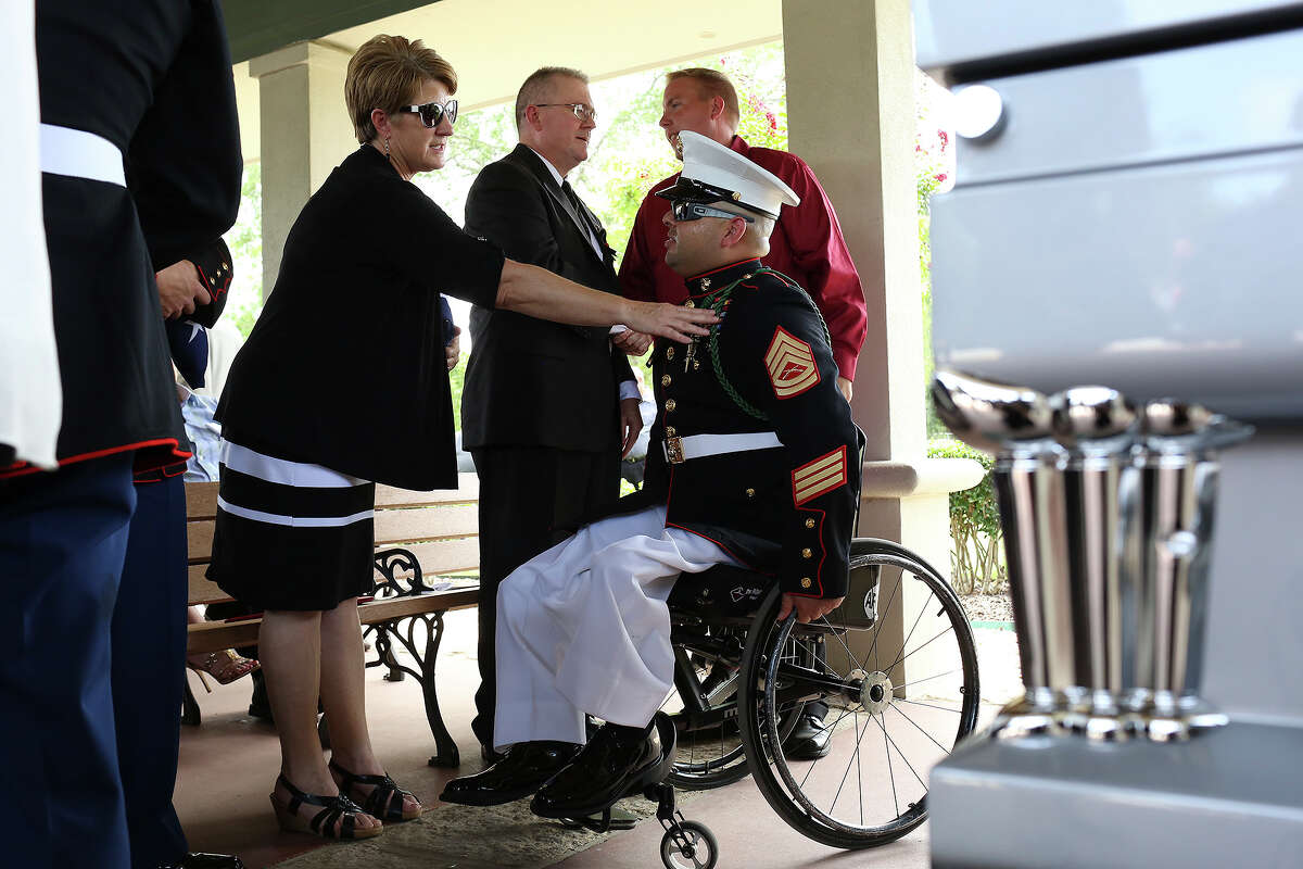 Jean Spitzer, center, the mother of Marine Sgt. Thomas Spitzer, talks with Marine Gunnery Sgt. Guillermo Tejada after the burial service for Sgt. Spitzer at Ft. Sam Houston National Cemetery in San Antonio on Monday, July 7, 2014. Sgt. Thomas Spitzer was killed in action in Hemland Province, Afghanistan on June 25, 2014. Gunnery Sgt. Tejada was injured in Afghanistan and lives across from the family of John Farias, Sgt. Spitzer's close friend who was killed in Afghanistan in 2011.