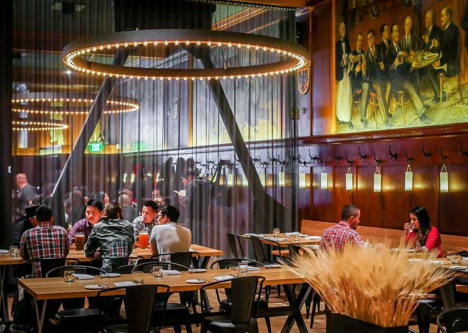 Venerable Financial District German restaurant Schroeder's has been reinvented, with lighting on the 1930s wall murals and floor-to-ceiling black mesh curtains to define the various areas. Photo: John Storey, Special To The Chronicle