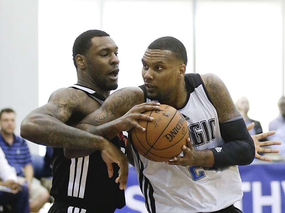Orlando Magic's Romero Osby, right, looks for a way to the basket past Houston Rockets' Tarik Black. Photo: John Raoux, Associated Press