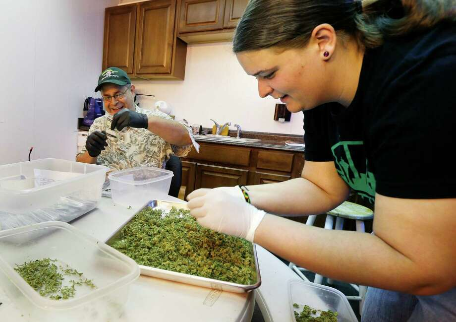 "In this photo taken July 1, 2014, workers Kristi Tobias, right, and Bruce Cumming prepare packets of a variety of recreational marijuana named ""Space Needle"" at Sea of Green Farms in Seattle. Workers at the grower, the first business licensed to grow recreational marijuana in Washington state, worked all weekend to have supplies ready for stores that were expected to be granted sale licenses on Monday, the day before the first day of legal recreational pot sales in Washington state. (AP Photo/Ted S. Warren) ORG XMIT: WATW405 Photo: Ted S. Warren / AP"