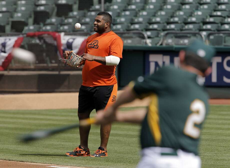 As Oakland coach Mike Gallego hits grounders in batting practice, the Giants' Pablo Sandoval engages in conversation. Photo: Carlos Avila Gonzalez, The Chronicle
