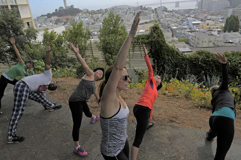 Hiking Yoga instructor Christiane Crawford leads a group in yoga exercises atop Russian Hill in June. Photo: Craig Hudson, The Chronicle