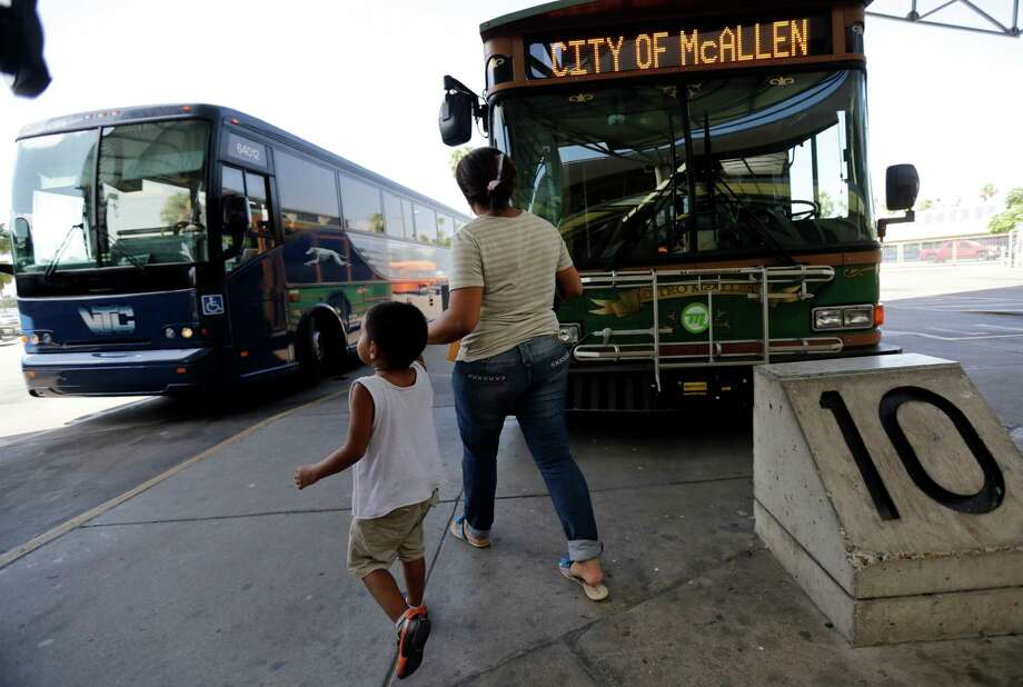In this June 20, 2014 photo, Cindy Jimenez, 26, from Olancho, Honduras, and her son depart the bus station in McAllen, Texas. Jimenez crossed illegally into the U.S. (AP Photo/Eric Gay) Photo: Eric Gay, STF / AP