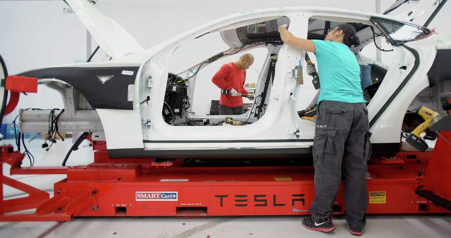 Workers add seat belts to a Tesla Model S sedan at the company's assembly plant in Fremont, Calif. Although the car's design has stayed the same since 2012, its functions continue to be updated electronically, even as it sits in the parking lot or garage. Photo: Noah Berger / Bloomberg / © 2013 Bloomberg Finance LP