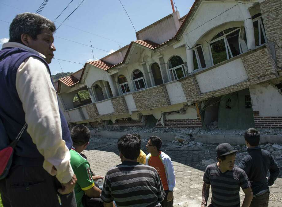 Neighbors gather outside homes that collapsed during an earthquake in San Pedro, Guatemala. There were also reports of power outages and rock slides on some roads in the nation. Photo: Oliver De Ros / Associated Press / AP