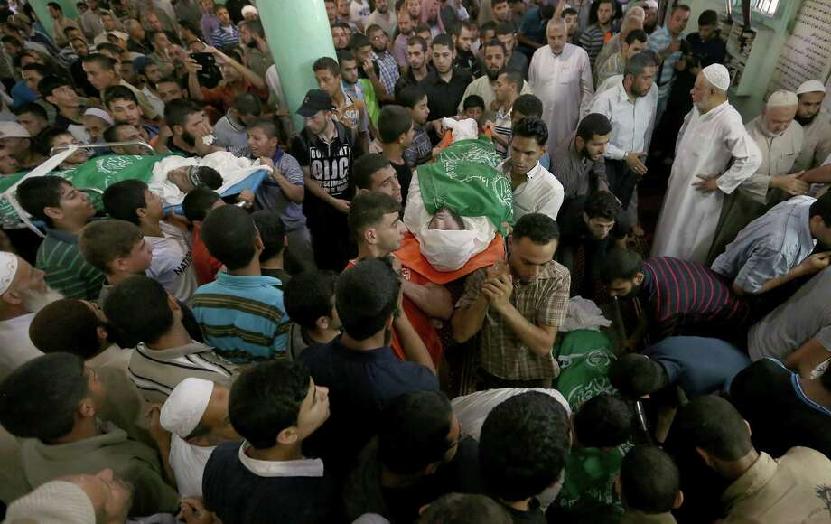 Palestinians carry bodies of the Ezz Al-Din Al Qassam Brigades members who were killed in an airstrike during a funeral in Rafah, southern Gaza Strip on Monday, July 7, 2014. The Islamic militant group Hamas that rules Gaza vowed revenge on Israel for the death of several of its members killed in an airstrike early Monday morning in the deadliest exchange of fire since the latest round of attacks began weeks ago. (AP Photo/Hatem Moussa) ORG XMIT: DV113 Photo: Hatem Moussa / AP