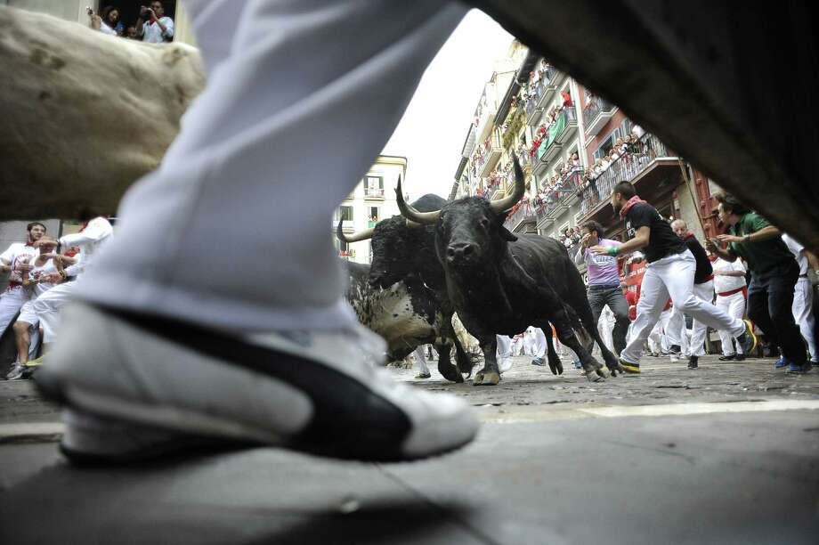 Participants run in front of Torrestrella ranch's bulls during the first bull run of the San Fermin Festival. Photo: ANDER GILLENEA, Stringer / AFP