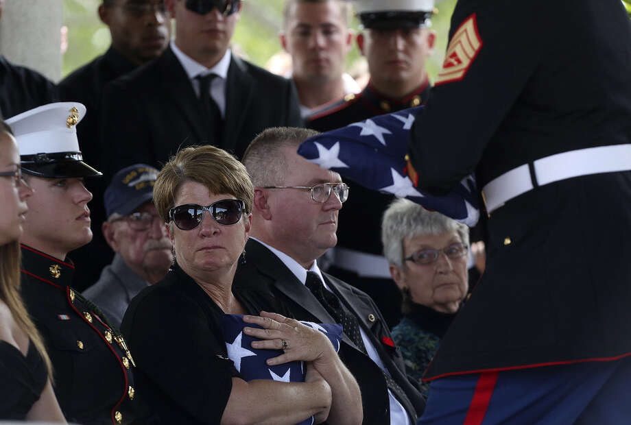 Jean Spitzer (center), the mother of Marine Sgt. Thomas Spitzer, watches as her younger son, Marine Lance Cpl. Nicholas Spitzer, is presented with a flag. The fallen Marine's fiancée, Casey Neef (left) and his father, John Spitzer (right), flank them. Photo: Photos By Lisa Krantz / San Antonio Express-News / SAN ANTONIO EXPRESS-NEWS