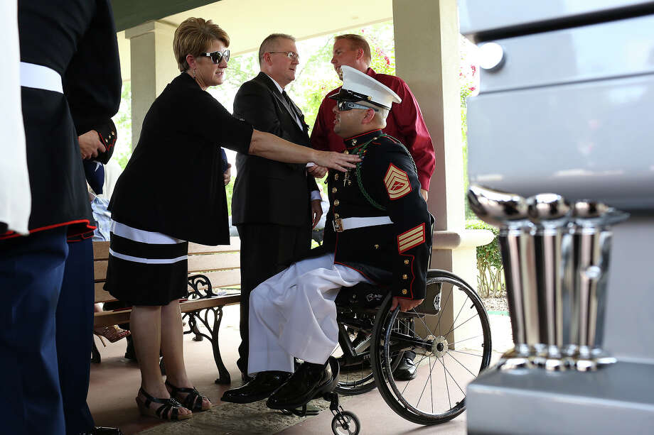 Jean Spitzer, center, the mother of Marine Sgt. Thomas Spitzer, talks with Marine Gunnery Sgt. Guillermo Tejada after the burial service for Sgt. Spitzer at Ft. Sam Houston National Cemetery in San Antonio on Monday, July 7, 2014. Sgt. Thomas Spitzer was killed in action in Hemland Province, Afghanistan on June 25, 2014. Gunnery Sgt. Tejada was injured in Afghanistan and lives across from the family of John Farias, Sgt. Spitzer's close friend who was killed in Afghanistan in 2011. Photo: SAN ANTONIO EXPRESS-NEWS / SAN ANTONIO EXPRESS-NEWS