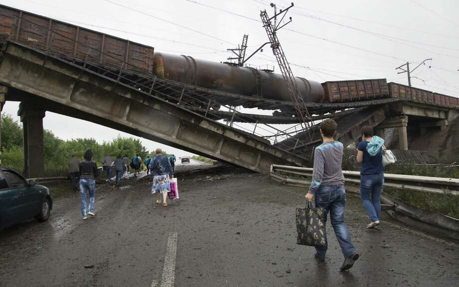 People walk under a destroyed railroad bridge over a main road leading into the eastern Ukraine city of Donetsk. Photo: Dmitry Lovetsky / Associated Press / AP