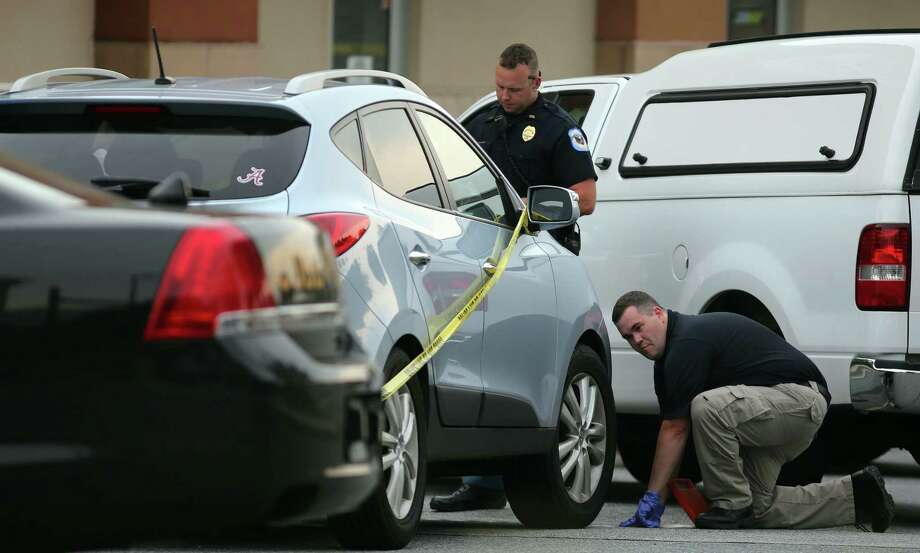 Police in Cobb County, Ga., check an SUV where Cooper Harris was left for about seven hours and died June 18 after his father, Justin Harris, forgot to drop him off at day care and went to work. Harris was charged with murder and child endangerment. Photo: Ben Gray / Atlanta Journal-Constitution / Atlanta Journal-Constitution