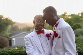 Markel Belser (right) and De'Mario Mims (left), both from Richmond, wed on April 18, at a private home overlooking Mount Diablo in Orinda. The pair entered and won a contest for a wedding give-away. Here, the two grooms embrace at their wedding.