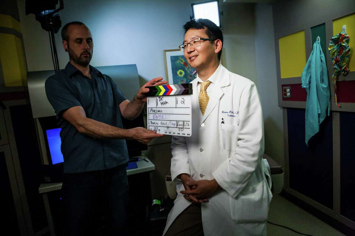 Dr. Winston Huh stands in while Christopher Beauchamp gets a slate before an interview on Friday for a documentary about James Ragan, whom Dr. Huh treated. Ragan died of cancer in February 2014. He was 20.