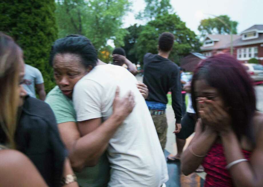 In this Saturday, July 5, 2014 photo, Georgia Utendahl, left, and Shanice Smith, right, grieve after learning that their family member was shot by police on Chicago's South Side. The Fourth of July weekend was a bloody one in Chicago, where at least nine people were shot to death and at least 60 others were wounded. (AP Photo/Sun-Times Media, Alex Wroblewski)  MANDATORY CREDIT, MAGS OUT, NO SALES ORG XMIT: ILCHS504 Photo: Alex Wroblewski / Sun-Times Media