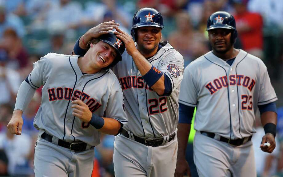 Kiké Hernandez, left, Carlos Corporan, center, and Chris Carter enjoy a happy homecoming after scoring on Marwin Gonzalez's triple in the second Monday. Photo: Tom Pennington, Staff / 2014 Getty Images