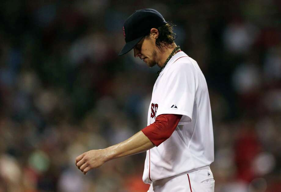 Boston Red Sox starting pitcher Clay Buchholz heads to the dugout after top of the fourth inning of a baseball game at Fenway Park in Boston, Monday, July 7, 2014.  Buchholz gave up a three-run, home run to Chicago White Sox' Dayan Viciedo in the inning. (AP Photo/Charles Krupa) ORG XMIT: MACK110 Photo: Charles Krupa / AP