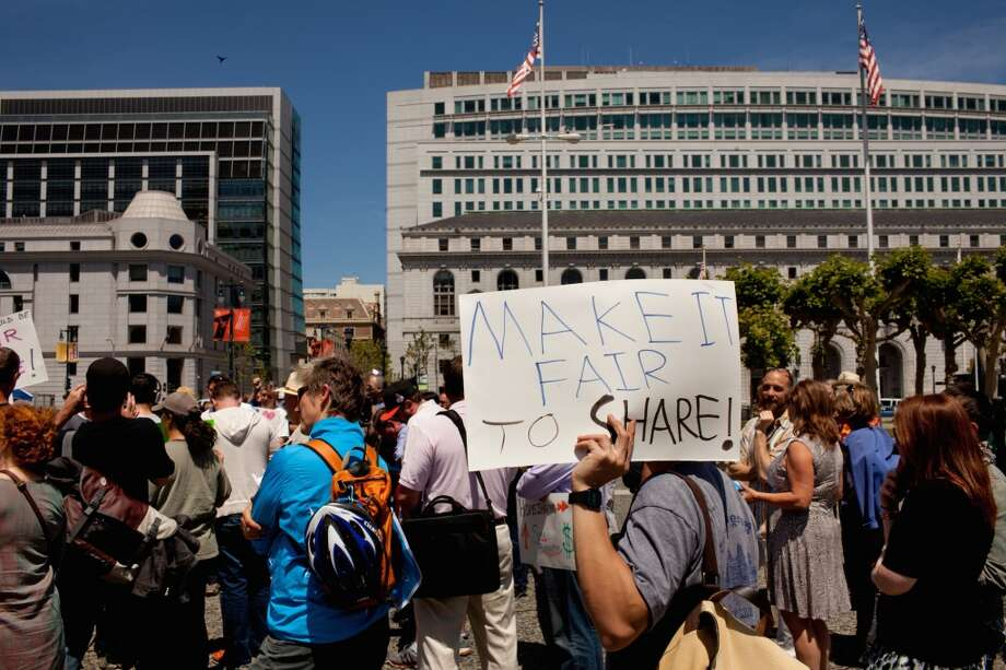 Stillman Wong, a house share supporter, covers the sun with his sign at a rally at the Civic Center Plaza in San Francisco, Calif. on Tuesday, April 29, 2014. Supporters came out to discuss a ballot initiative that would limit short-term rentals in San Francisco. Photo: Special To The Chronicle