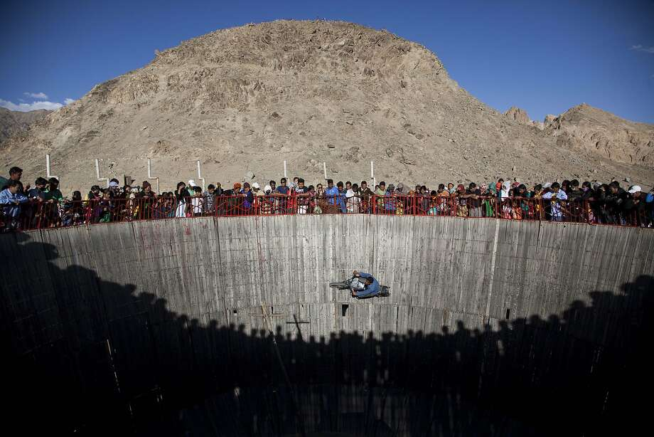 Buddhist devotees and others watch an Indian man perform bike stunts on the fifth day of Kalachakra near Leh, India, Monday, July 7, 2014. Buddhist devotees from across the globe have arrived in this Himalayan region of Ladakh to attend the 'Kalachakra' or Wheel of Time initiations by the Dalai Lama that began Thursday.  (AP Photo/Tsering Topgyal) Photo: Tsering Topgyal, Associated Press