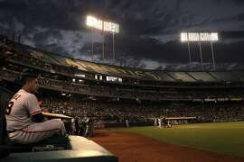 Hector Sanchez, left, waits during a review in the fifth inning as the Oakland Athletics played the San Francisco Giants on Monday, July 7, 2014, at O.co Coliseum in Oakland, Calif.