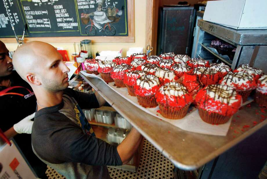 FILE - In this Sept. 20, 2007 file photo, Crumbs Bake Shop managing partner Harley Bauer carries of tray of cupcakes during the store's grand opening in Beverly Hills, Calif. Crumbs on Monday, July 7, 2014 said it is shuttering all its stores, a week after the struggling cupcake shop operator was delisted from the Nasdaq. Photo: Matt Sayles, AP / R-SAYLES