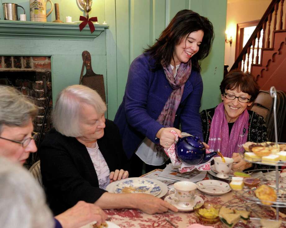 "Brigid Guertin, standing, executive director of the Danbury Museum and Historical Society, on Main Street in Danbury, Conn., serves tea at the museum's annual fundraiser, ""Holiday Tea in the Rider House.""  From left are Barbara Lynch, Kathy Jacocks and Mary Tomaino, all of Danbury. Photo: Carol Kaliff / The News-Times"