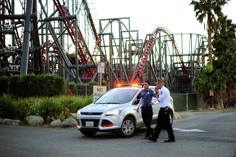 Members of the Six Flags Magic Mountain amusement park security staff monitor the situation at the exit of the park after riders were injured on the Ninja coaster Monday, July 7, 2014, in Valencia, Calif. The roller coaster hit a tree branch dislodging the front car, leaving four people slightly injured and keeping nearly two dozen summer fun-seekers hanging 20 to 30 feet in the air for hours as day turned to night. Two of the four people hurt on the Ninja coaster were taken to the hospital as a precaution, but all the injuries were minor, fire and park officials said. Photo: Andy Holzman, AP / Los Angeles Daily News