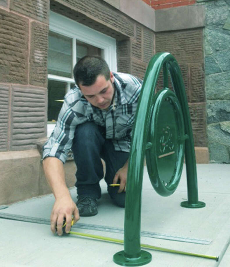 One of 12 bicycle racks planned for the town is carefully installed recently by Justin Woods of Sbc Constructuon of Winsted at the northwest corner of Roger Sherman Town Hall in New Milford.June 25, 2014 Photo: Norm Cummings / The News-Times