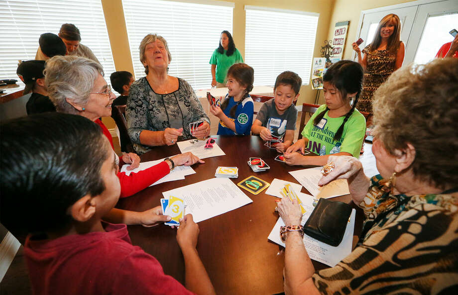 Eugenio Espleleta (at table from left), 8, Sara Schlereth, Norma Palmer, Holly Casanova, 6, Antonio Ramon Carter, 5, Kaylee Bowren, 8, and Mary Lou Saner play a lively game of Uno. Photo: Photos By Marvin Pfeiffer / Stone Oak Weekly / Express-News 2014