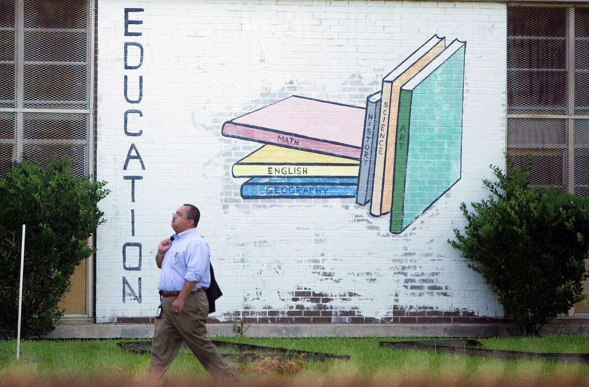 HISD Chief Operating Officer Leo Bobadilla walks outside the vacant Terrell Middle School, Tuesday, July 8, 2014, in Houston. Federal officials toured the closed campus as a potential choice for housing immigrant children who have crossed the border alone.