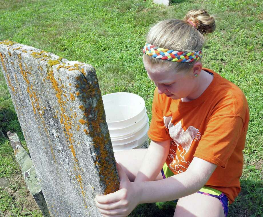 Mairead Derby, 13, scrubs at headstone at the Greenfield Hill Cemetery,during one of the community service days for the Future Leaders Camp at Wakeman Boys and Girls Club. Photo: Genevieve Reilly / Fairfield Citizen
