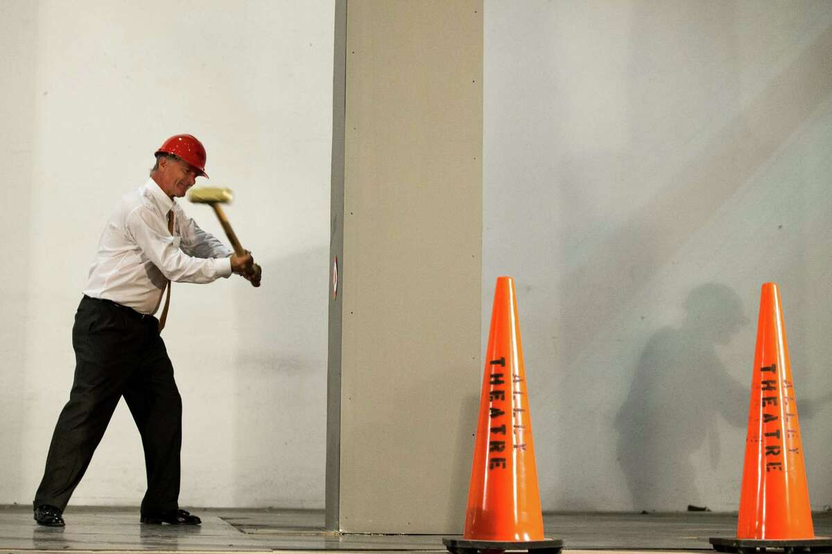 Roger Plank, co-chair of the Alley Theatre capital campaign, swings a sledgehammer on a column on the stage during a