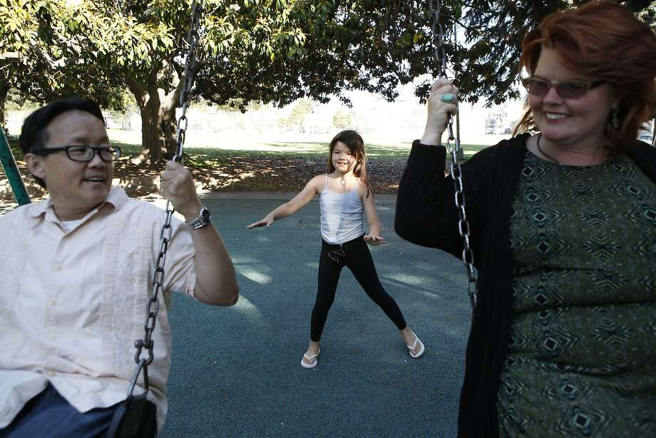 Chino Scott-Chung (left) and Maya Scott-Chung play in San Antonio Park in Oakland with their 9-year-old daughter, Luna. Photo: Michael Short, The Chronicle