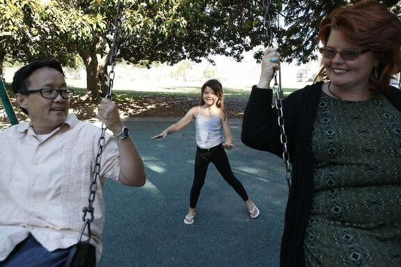 Chino Scott-Chung, left, and Maya Scott-Chung play on the swings San Antonio Park with their daughter Luna(9) in Oakland, CA, Thursday, July 3, 2014.