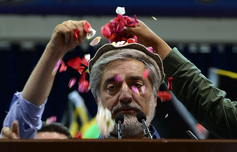 Presidential candidate Abdullah Abdullah is showered with rose petals by supporters as he speaks at a rally in Kabul. He blamed fraud for his second-place finish in preliminary results. Photo: Shah Marai, AFP/Getty Images
