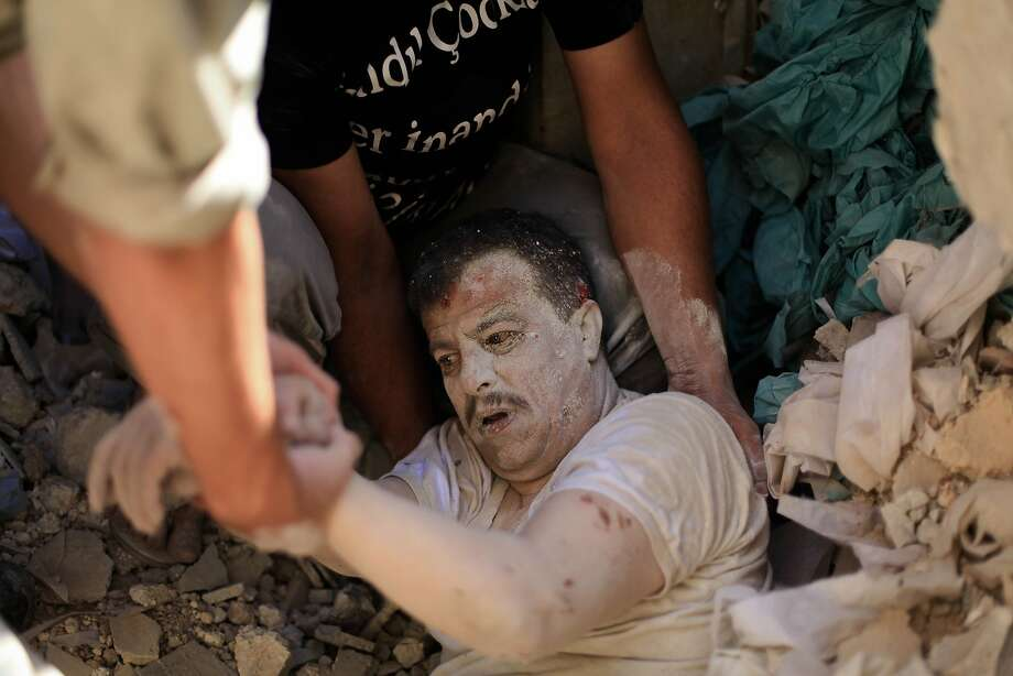 Bombing survivor:Members of Syrian Civil Defense rescue a man trapped under rubble following a reported barrel-bomb attack by government forces in the Qadi Askar neighborhood in Aleppo. Photo: Ahmed Deeb, AFP/Getty Images