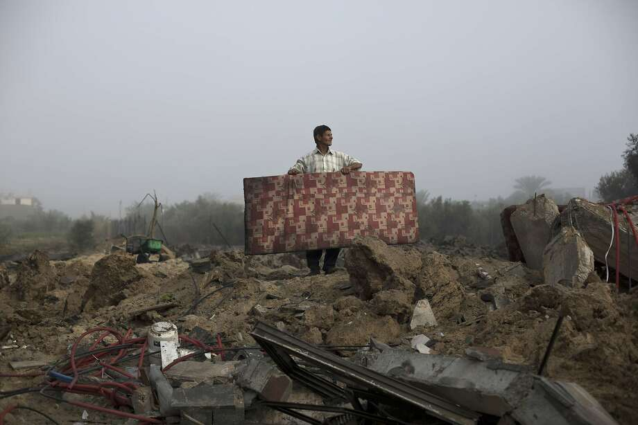 Israel retaliates:A Palestinian man salvages a mattress from the   rubble of a building destroyed by an Israeli military strike in Khan Yunis, southern Gaza Strip.   Israeli warplanes pounded Gaza with more than 50 strikes, killing at least 15 people, after Hamas   militants fired scores of rockets over the border. Photo: Mohammed Abed, AFP/Getty Images