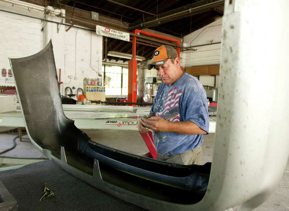 Gary Cunningham works on a car at Grover C. Cunningham Auto Body Shop, the shop he owns with his father, Bruce, in Greenwich, Conn., on Tuesday, July 8, 2014. Photo: Lindsay Perry / Stamford Advocate