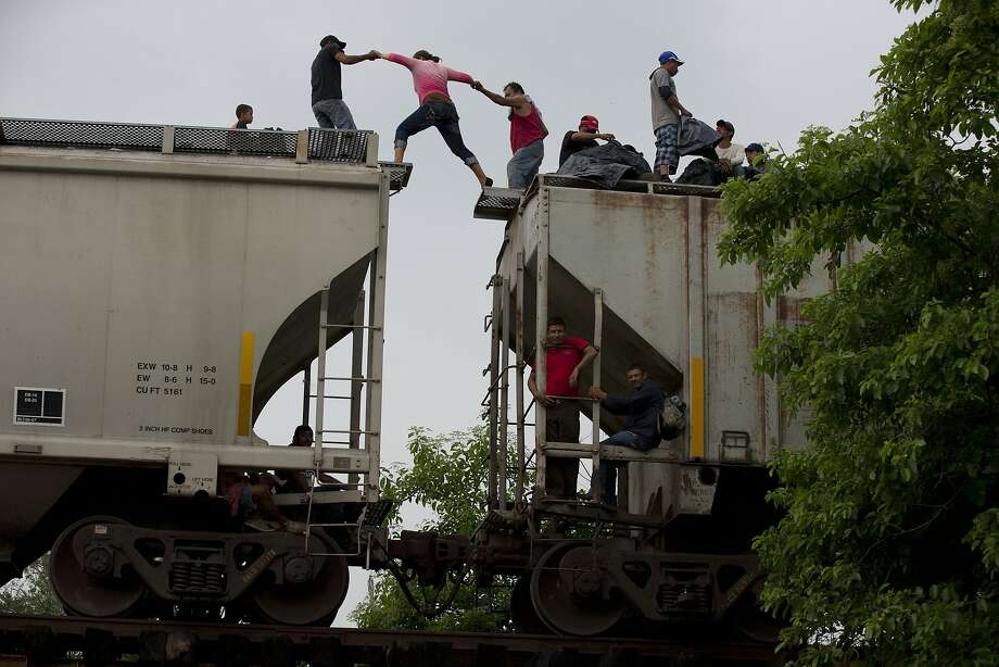 A woman is helped from one boxcar to another in June as other Central American migrants wait atop a train they were riding, hours after a minor derailment outside Reforma de Pineda, Chiapas state, Mexico. Photo: Rebecca Blackwell, Associated Press