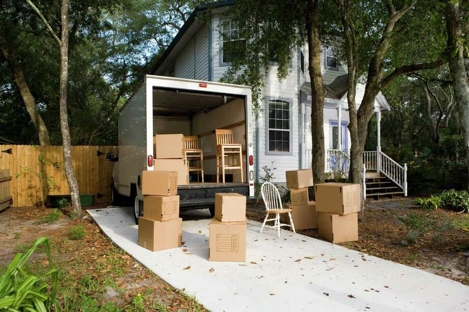 Moving van with cardboard box and chairs by house Photo: Purestock / Purestock